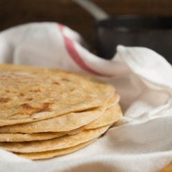 An upclose shot of a stack of paratha in a white kitchen towel