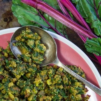 beet greens curry on a pink plate with silver spoon