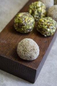 Date bites with pistachios, poppy seeds and almond coating on a piece of dark wood