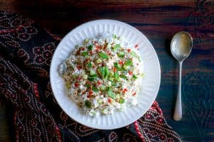 A white bowl of Cucumber Raita with a spoon on the side
