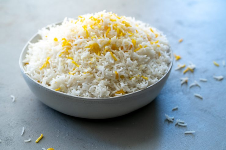 A bowl of basmati rice with some yellow saffron rice for color