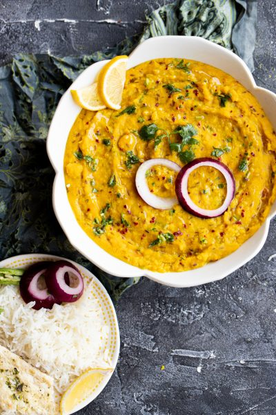 moong dal (yellow lentils) in a white bowl garnished with lemon slices, raw red onion and cilantro with a small plate of rice and naan on the side